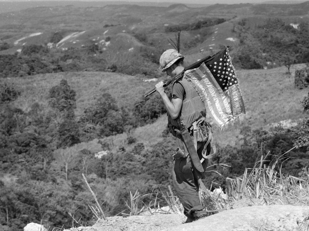 A U.S. Marine carries an American flag on his rifle during a recovery operation