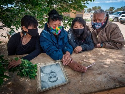 The Covid-19 pandemic has exacted a heavy toll on Native American communities. In this May 2020 image, Navajo elder Emerson Gorman (R) sits with his (L-R) daughter Naiyahnikai, wife Beverly and grandchild Nizhoni near the Navajo Nation town of Steamboat in Arizona.