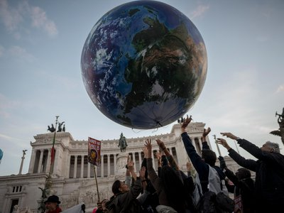 A crowd sends aloft a balloon representation of Earth at Piazza Venezia during a climate change rally in Rome a day before the COP21 conference in Paris.