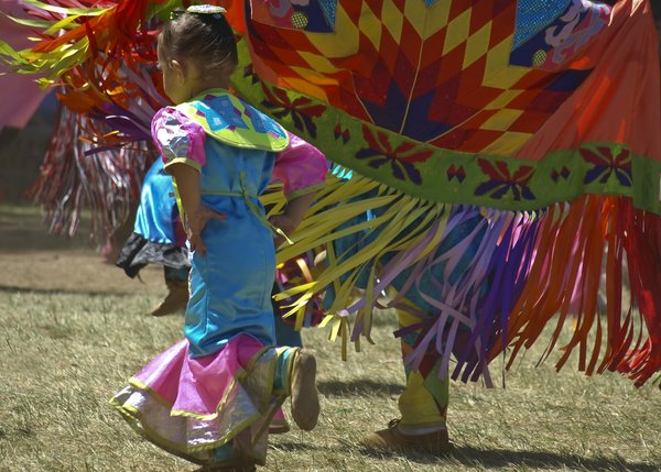 A young American Indian girl learns her dance steps from her grandmother at the traditional tribal gathering. thumbnail