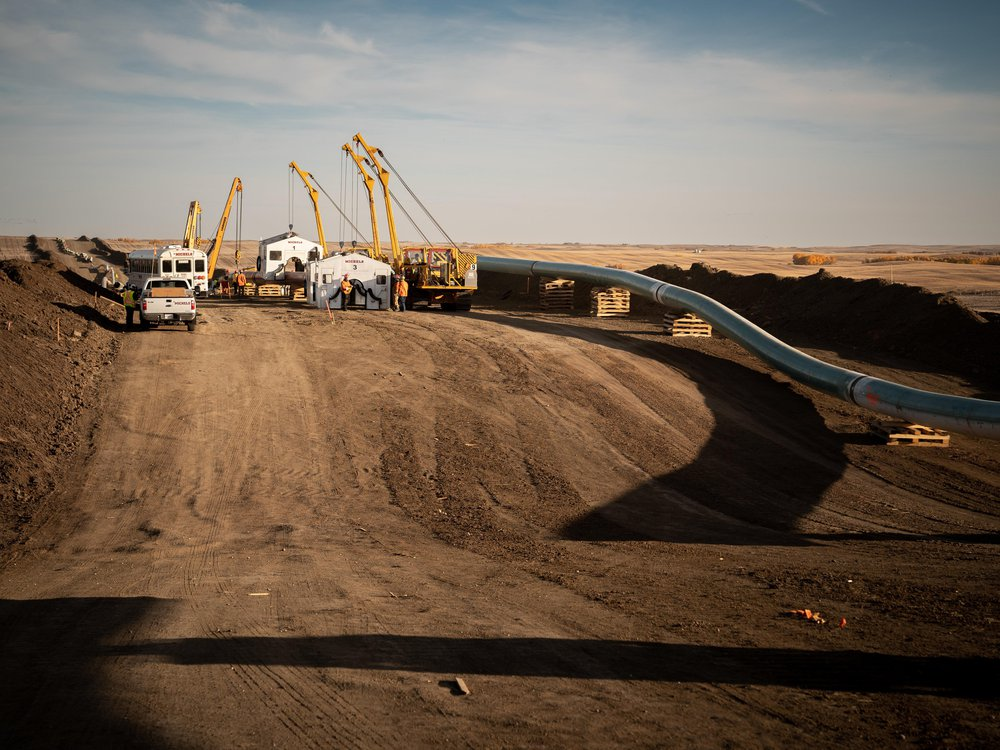 Five construction cranes, a truck and a bus sit atop a dirt road alongside pipeline, flanking the right side of the image.