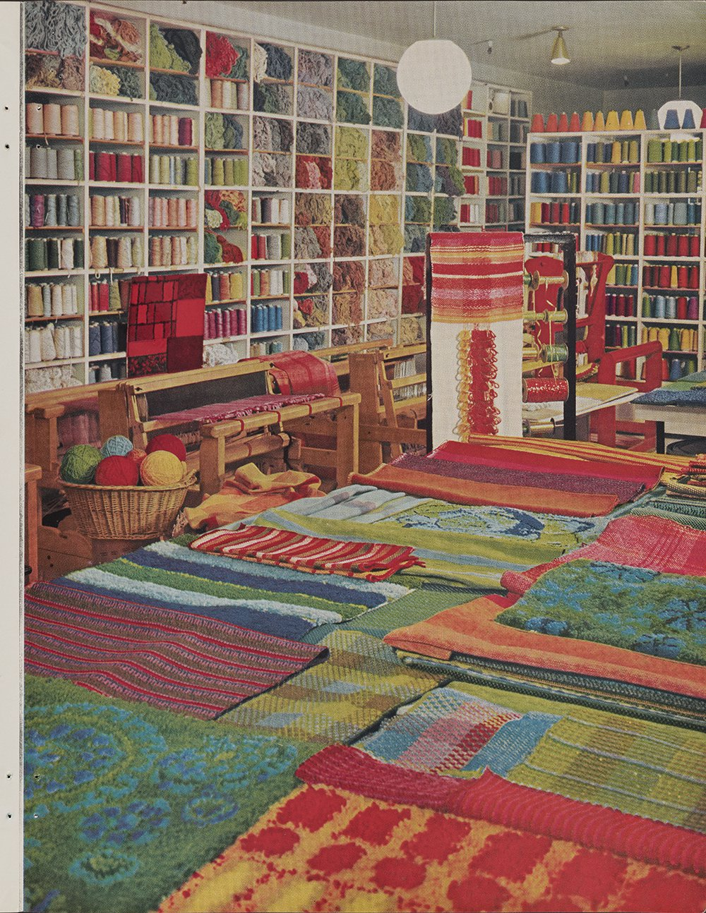 Textile showroom with ceiling-high shelves with yarn and thread lining the walls and layers of colorful rugs displayed on the floor.