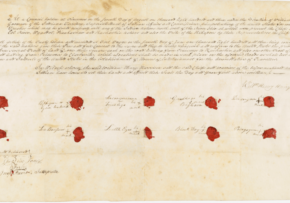 A treaty on a sheet of horizontal parchment paper, with red wax seals next to 11 signed names and three paragraphs of text written in neat, sloping cursive