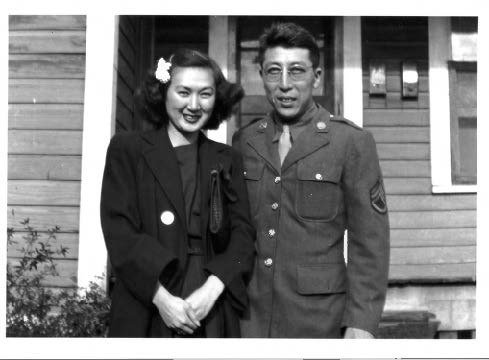 Black and white image of couple standing in front of house