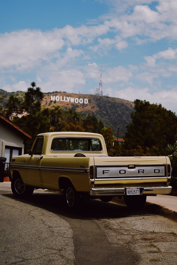 A pale yellow vintage Ford pickup truck under the Hollywood Sign thumbnail
