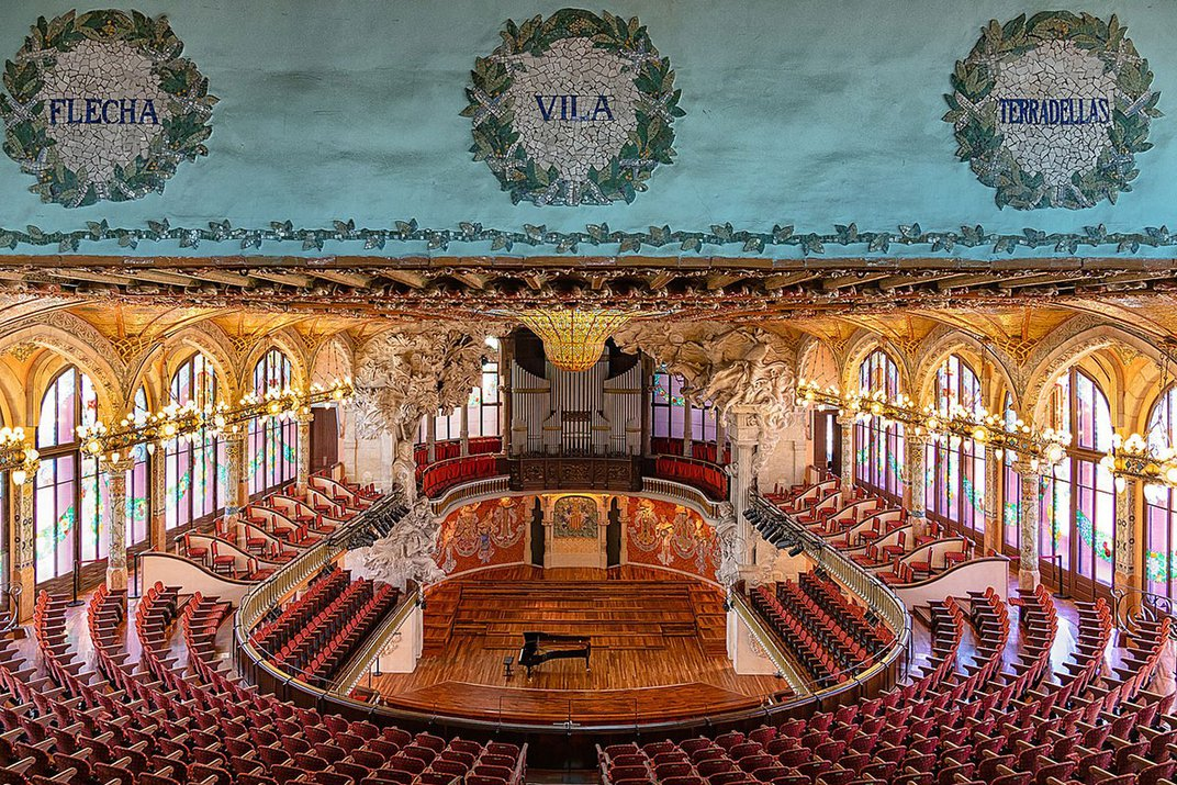 Interior of a music hall, with tiered seating arranged in a horseshoe shape. It is lit up by arched windows on either side.