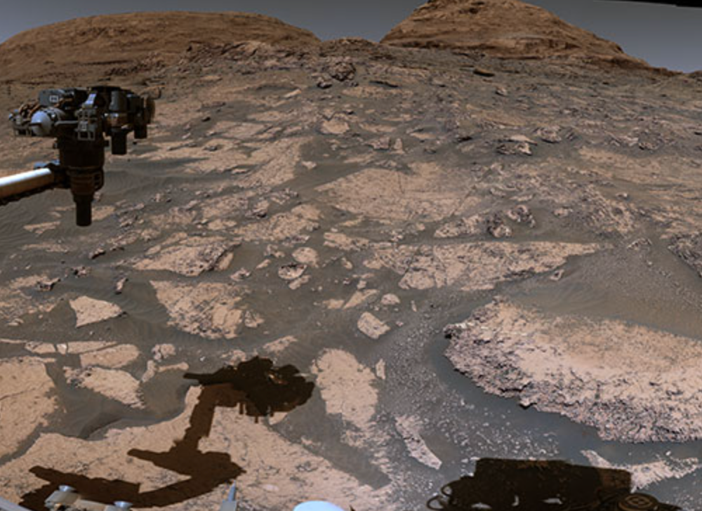 An image taken with the Curiosity Mars Rover. The image showed the Mars's dusty surface and a few hills in the background. The rover's arm is also seen in the photo.