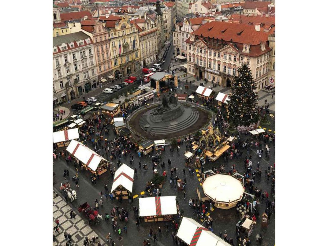 Aerial view of an outdoor market with tents set up in a city plaza.