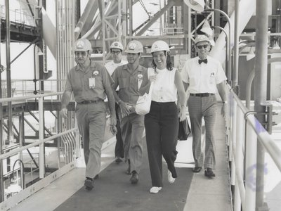 Ann Montgomery, lead crew systems engineer during the Apollo program, on the swing arm of the launch pad at Kennedy Space Center with other NASA employees, circa 1970.