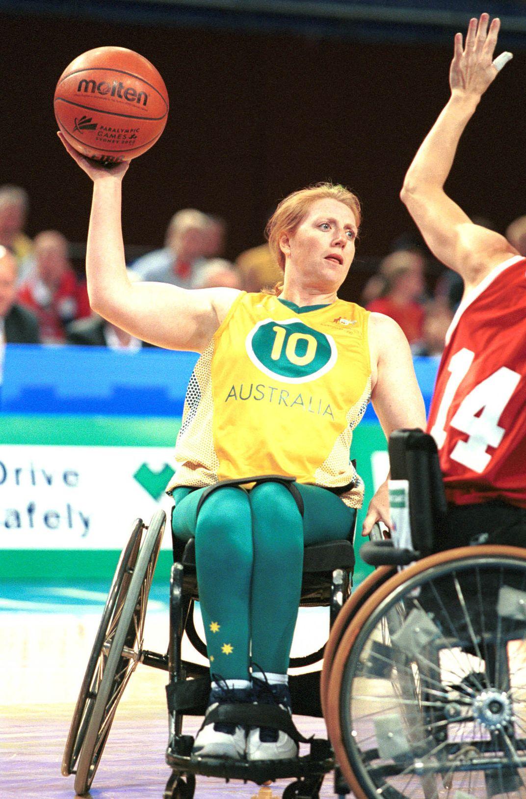 Woman passes ball during wheelchair basketball game