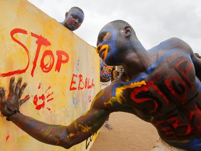 An actor, playing the role of a vaccine against Ebola, performs at a school in Abidja, Ivory Coast, last September