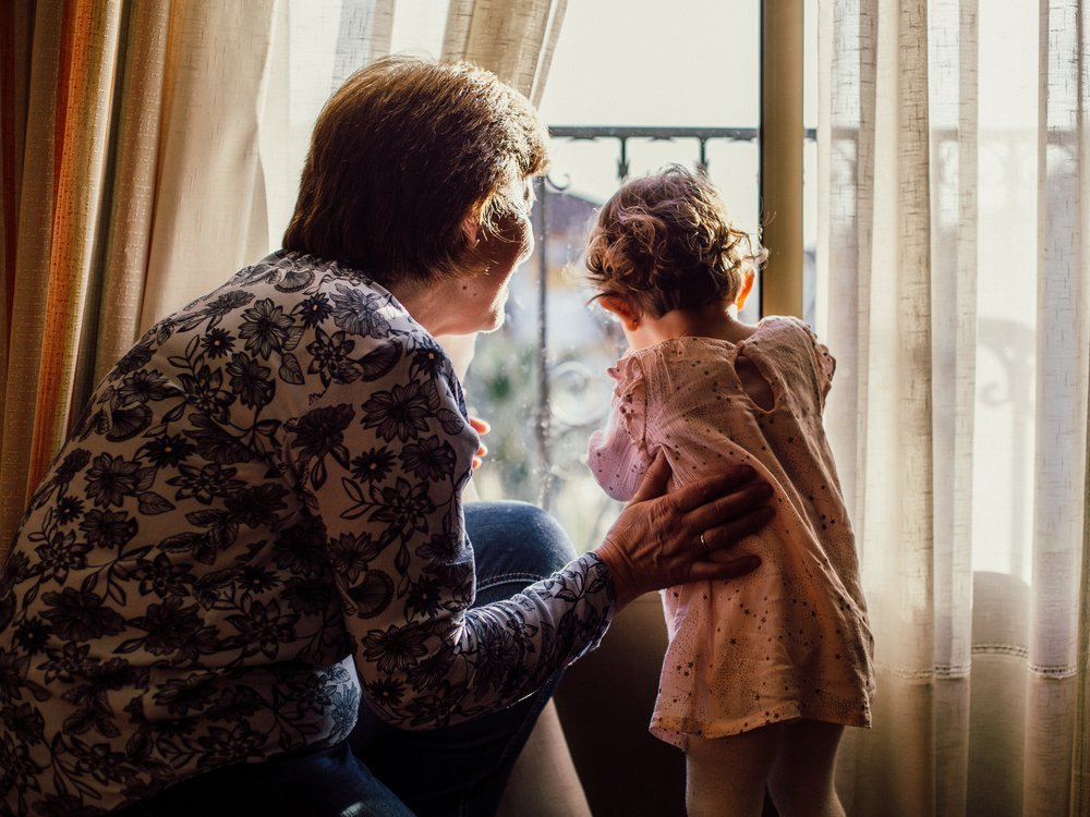 Grandmother and child looking out window