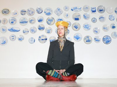 Julie Green poses in front of a selection ofThe Last Supperplates in 2015. The artist died on October 12 at age 60.
