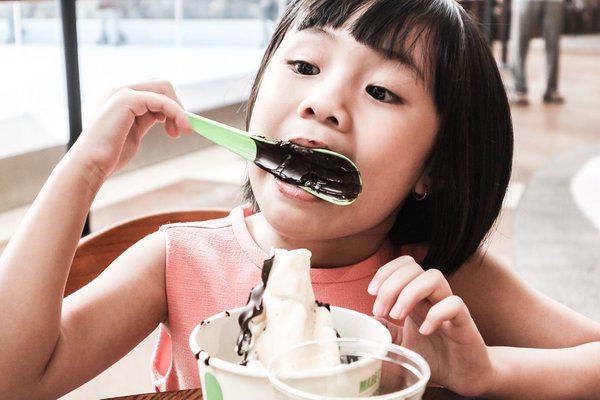 Little girl enjoy chocolate spoon thumbnail