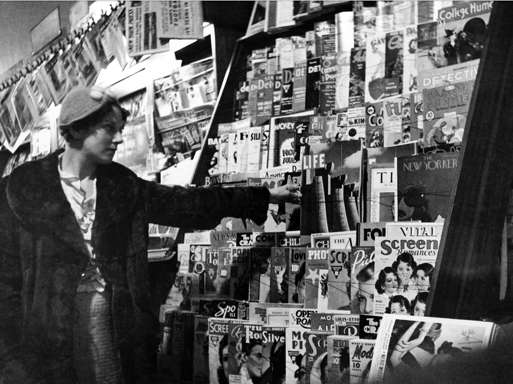A black and white image of a young woman, wearing a cap and fur coat, reaching for a copy of Life on a crowded newsstand; a copy of the New Yorker and Time are also in view