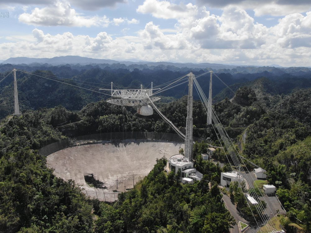 A photograph of the dish from high above. It has three tall towers around the circular dish, all connected by thick cables. The dish has a 100-foot hole on the side. The observatory is surrounded by expansive forest.