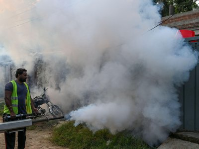 In residential district of Lahore, a health worker fumigates to kill off mosquito larvae to combat the spread of dengue.