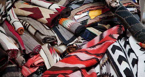 A potential buyer must carefully inspect the rugs at the Navajo rug auction