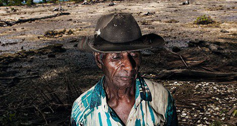 Posakei Pongap, a Manus islander, in front of a field ruined by salinization.