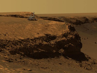 An  artist's concept of the Mars Exploration Rover Opportunity superimposed on a photo of Victoria Crater, taken by the rover.