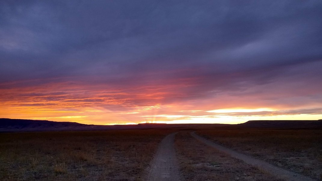 A dirt road cuts through Shirley Basin, a grassland in Wyoming, around sunrise.