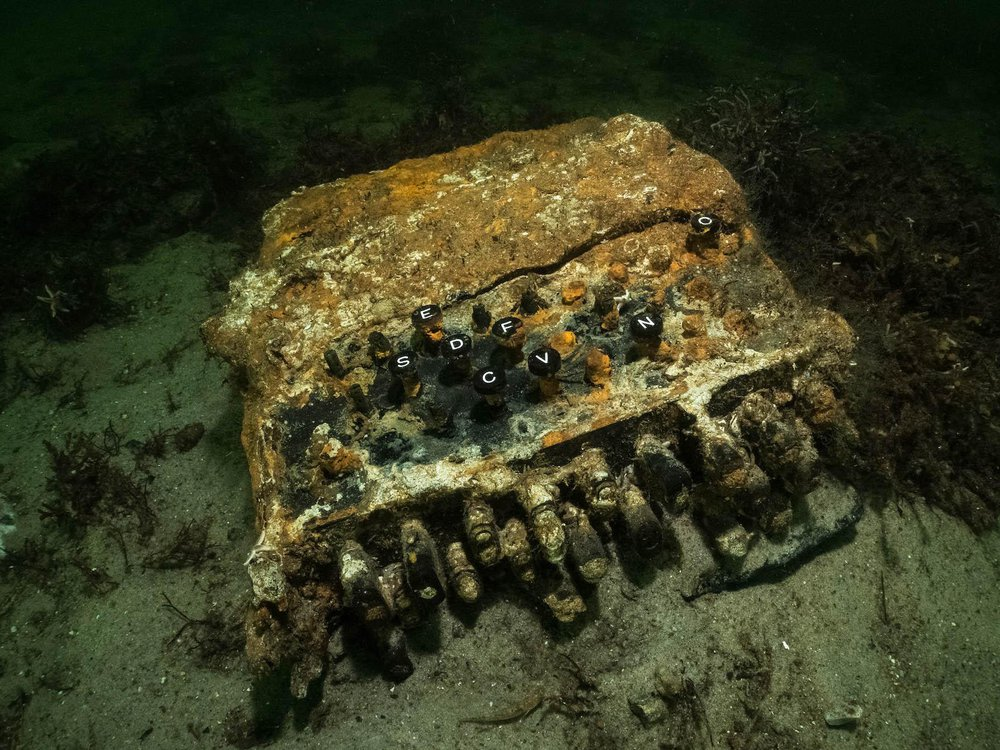 A close-up shot of the rusted machine at the bottom of the ocean, a bit overgrown with orange-y algae but with its keys, like a typewriter's, still discernable