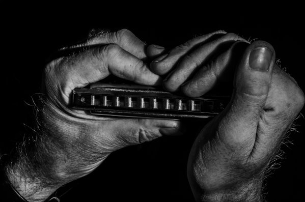 Hands holding old harmonica thumbnail