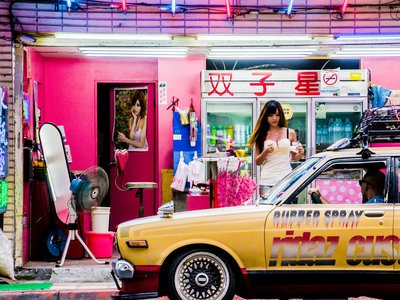 """A sidewalk vendor, known as a """"betel nut beauty,"""" sells snacks on a curb in New Taipei."""