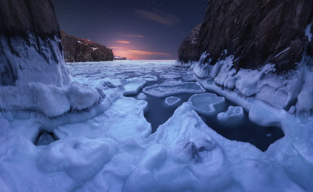 A rocky ridge on the coast of the Sea of Japan. The coast is surrounded by piles of ice.