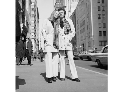 Swedish designer Sighten Harrgard and his fiancee model a unisex belted jacket and scarf with wide-legged double-knit trousers—March 1969.