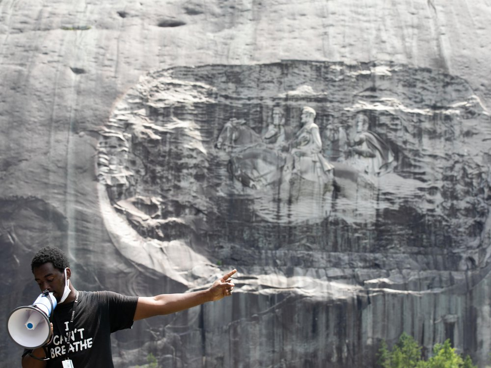 A Black man wears a black and white t shirt and stands with a megaphone, gesturing to the Confederate monument on the face of a gray granite rock behind him