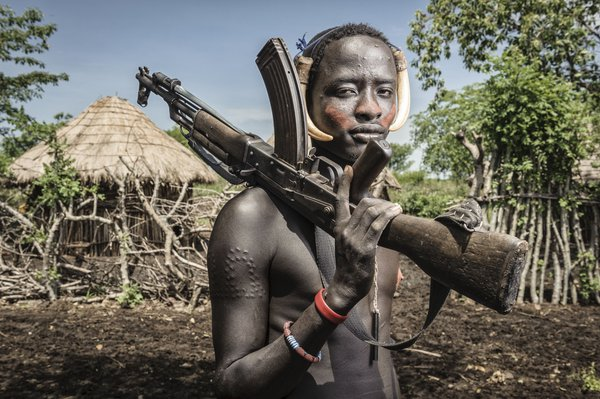 Portrait of a young mursi man holding a kalashnikov, Omo valley, Ethiopia thumbnail