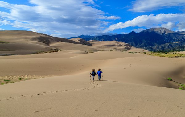Two children hike into the expanse of the Great Sand Dunes thumbnail