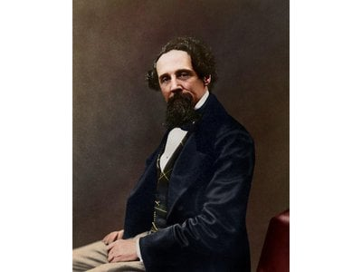 The colorized photograph shows 47-year-old Dickens in a blue, green and yellow waistcoat; a navy blue jacket; and tan trousers.