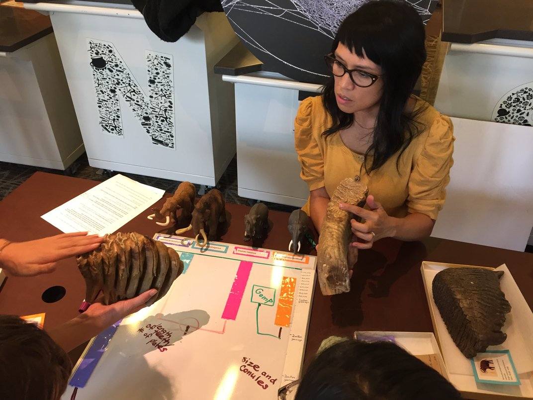 Woman with glasses and dark hair at a wood table holding a 3-D scanned fossil, teaching museum visitors about fossils and science.
