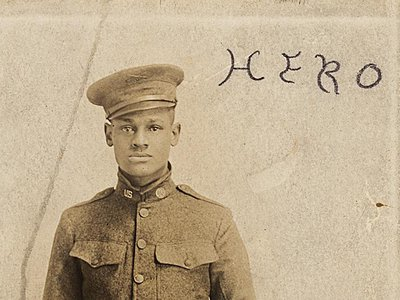 """Cpl. Lawrence McVey poses at attention in a photographic postcard. The word """"Hero"""" is inscribed at the top."""