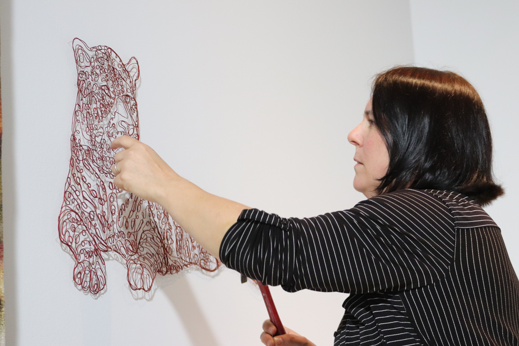 Artist nails string in the shape of a jaguar to a white wall