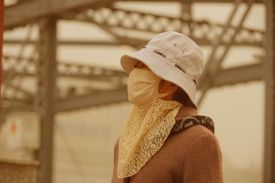 A woman wearing a face mask walks on a road in a sandstorm in Lanzhou city, northwest Chinas Gansu province, 24 April 2014 Credit: Imaginechina/Corbis