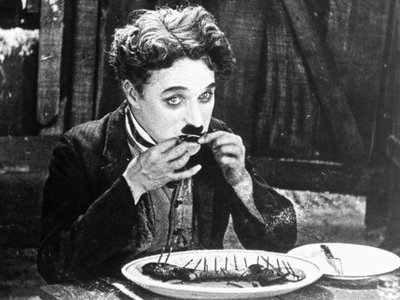 Charlie Chaplin eats his shoe in The Gold Rush (1925).