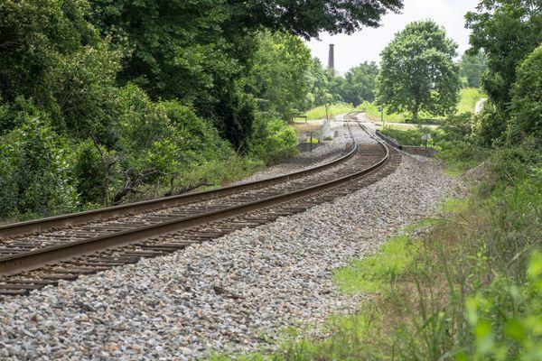 Train tracks leading towards an old factory. thumbnail