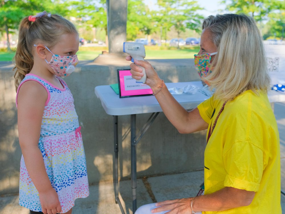 A young girl wearing a colorful cloth mask (left) gets her temperature read by a woman at the Childhood Development and Learning Lab at Central Michigan University