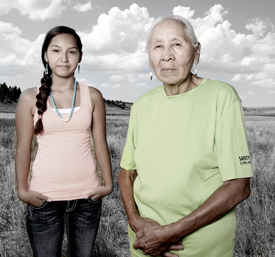 Two women stand in a field.