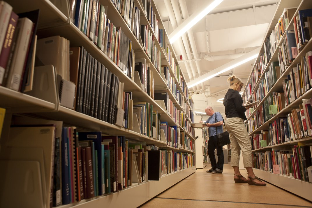 Photo of a man and woman perusing library shelves.