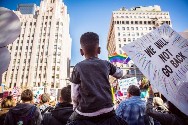 Child Waving Gay Pride Flag on Father's Shoulders at The Women's March thumbnail