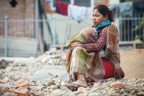 Nepali Woman Sitting on top of Earthquake Rubble thumbnail