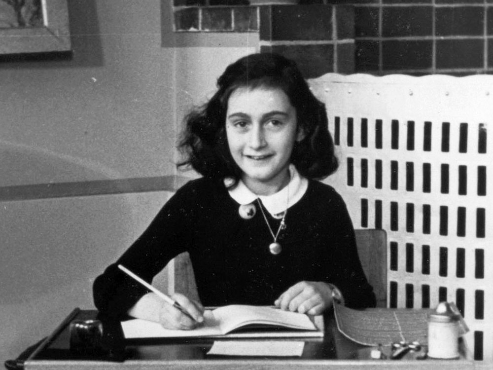 A young Frank sits at a school desk, notebook open and pencil poised to write, smiling and wearing a school uniform