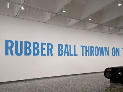 """Lawrence Weiner's """"A RUBBER BALL THROWN ON THE SEA, Cat. No. 146"""" is displayed at the Hirshhorn Museum in blue, sans-serif lettering. Weiner was open to the seven words being produced in any color, size or font."""