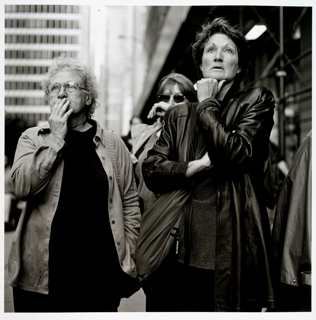 A black and white photograph of three women. They are all looking at the same spot in the near distance and have shocked expressions on their faces.