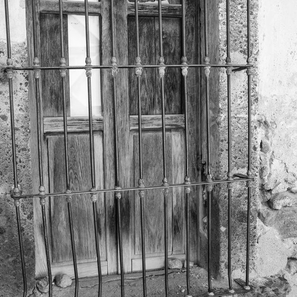 Shuttered Window With Broken Panel Behind Wrought Iron Bars, Monochrome thumbnail