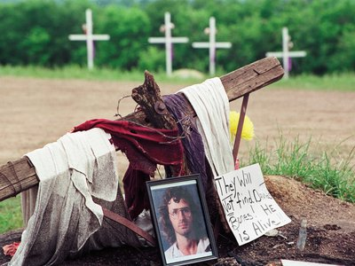 A photo of David Koresh rests beside a wooden cross as part of a monument erected in Waco, Texas, by supporters of the Branch Davidian leader and founder, Friday, April 30, 1993.